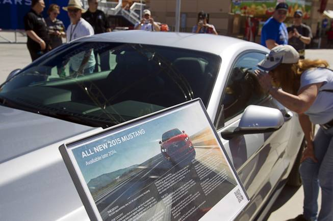 A woman looks into the redesigned 2015 Ford Mustang during the Mustang 50th Birthday Celebration at the Las Vegas Motor Speedway Thursday, April 17, 2014. The celebration continues through Sunday.