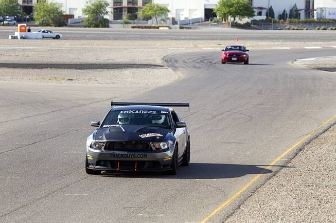 Late-model Mustangs are driven on a road course during the Mustang 50th Birthday Celebration at the Las Vegas Motor Speedway Thursday April 17, 2014.