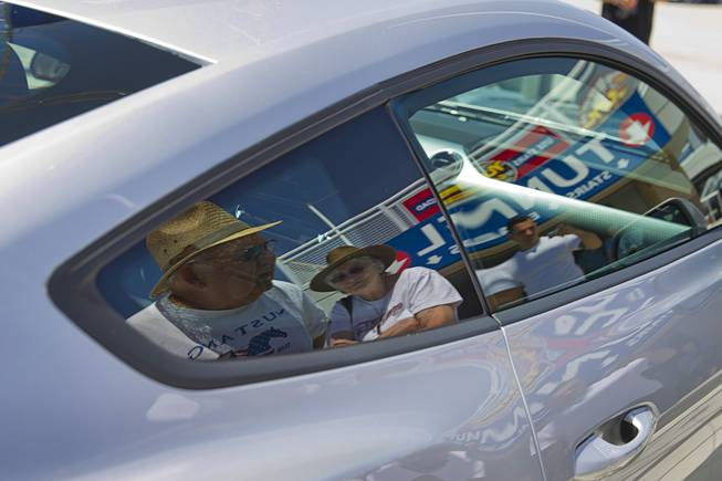 Jim Ramsden and his wife nancy of Salem, Oregon, are reflected in the window of a 2015 Ford Mustang during the Mustang 50th Birthday Celebration at the Las Vegas Motor Speedway Thursday, April 17, 2014. The celebration continues through Sunday.