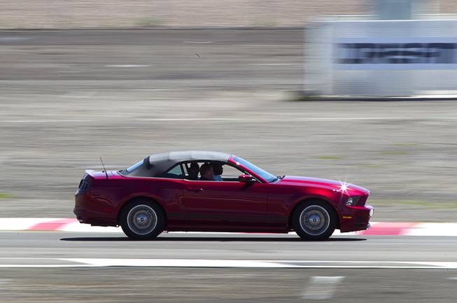 A late-model Mustang convertible drives on an infield course during the Mustang 50th Birthday Celebration at the Las Vegas Motor Speedway Thursday, April 17, 2014. The celebration continues through Sunday.