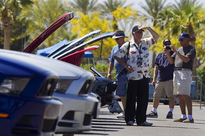 Paul Metcalfe, center, of New Zealand looks over classic Mustangs during the Mustang 50th Birthday Celebration at the Las Vegas Motor Speedway Thursday, April 17, 2014.