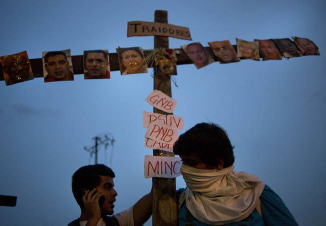 "Anti-government protesters carry a cross covered with photos of government officials and supporters under the Spanish word ""Traitors"" at a demonstration during Holy Week in Caracas, Venezuela, Wednesday, April 16, 2014. The opposition wants President Nicolas Maduro's government to free jailed opponents and create an independent truth commission to determine responsibility for deaths tied to protests that have rocked the nation since February."