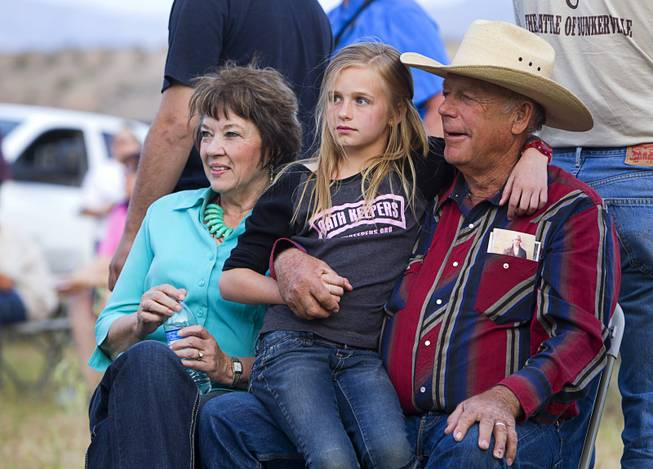 "Rancher Cliven Bundy, his wife Carol and his granddaughter Jerusha Bundy, 10, listen to live music  during a Bundy family ""Patriot Party"" near Bunkerville Friday, April 18, 2014. The family organized the party to thank people who supported Bundy in his dispute with the Bureau of Land Management."