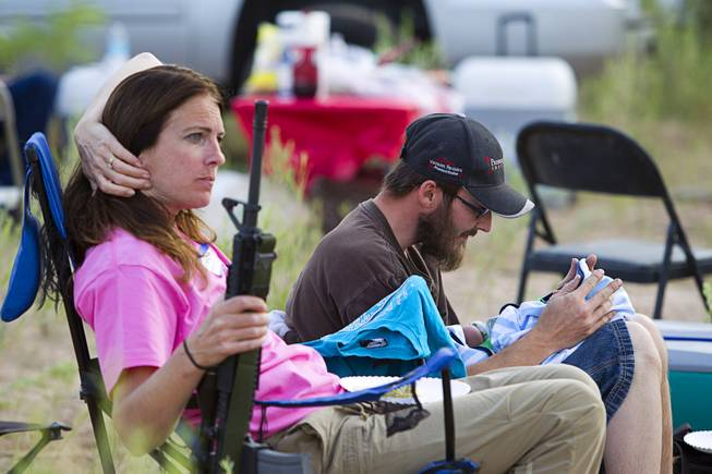 "Chris Shelton of Las Vegas interacts with his 1-week-old son as his mother Shelley Shelton holds his rifle during a Bundy family ""Patriot Party"" near Bunkerville Friday, April 18, 2014. The Bundy family organized the party to thank people who supported rancher Cliven Bundy in his dispute with the Bureau of Land Management."