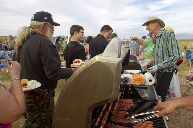 "Vinayak (no other name provided), right, works a food line during a Bundy family ""Patriot Party"" near Bunkerville Friday, April 18, 2014. The family organized the party to thank people who supported rancher Cliven Bundy in his dispute with the Bureau of Land Management."