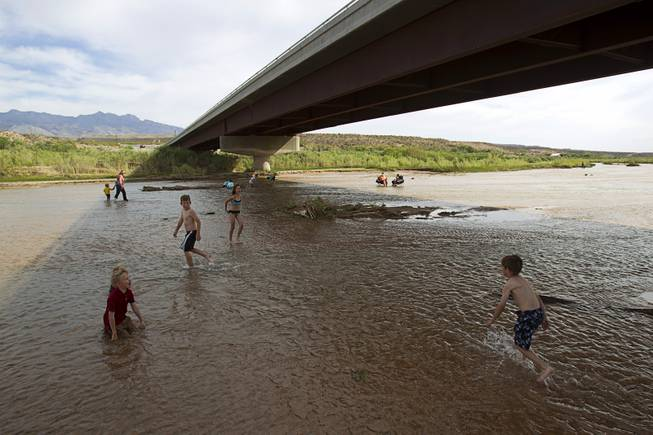 "Children play in the Virgin River during a Bundy family ""Patriot Party"" near Bunkerville Friday, April 18, 2014. The family organized the party to thank people who supported rancher Cliven Bundy in his dispute with the Bureau of Land Management."