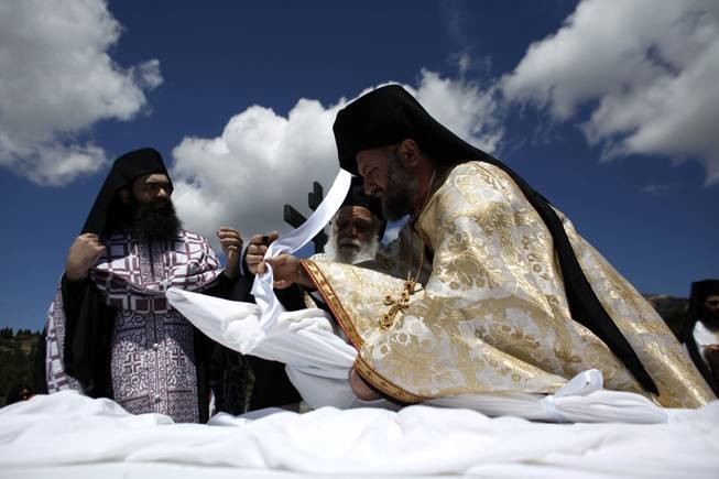 A Greek Orthodox priest wraps an icon of the body of Jesus with a sheet during a Good Friday reenactment  of Christ being taken down from the crucifix, at the Penteli Monastery, near Athens, on Friday, April 18, 2014. More than 250 million Orthodox Christians worldwide will celebrate Easter this year on Sunday, April 20.