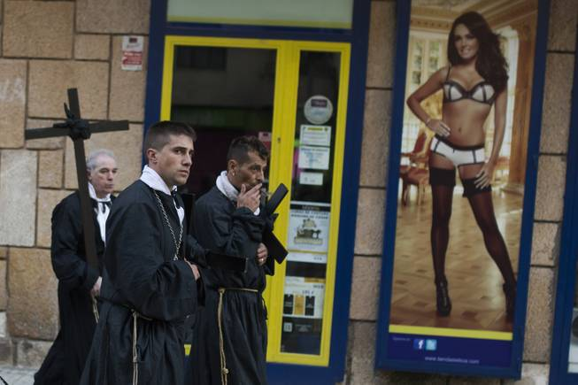 Penitents of the Jesus Nazareno brotherhood pass by a lingerie shop as they take part in a Holy Week procession in Zamora, northern Spain Friday, April 18, 2014. Hundreds of processions take place throughout Spain during the Easter Holy Week.