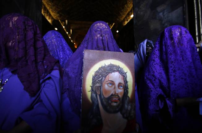 "Female penitents called ""Veronicas"" participate in a Good Friday procession carrying an image of Jesus in Quito, Ecuador, Friday, April 18, 2014. Holy Week commemorates the last week of the earthly life of Jesus Christ, culminating in his crucifixion on Good Friday and his resurrection on Easter Sunday. (AP Photo/Dolores Ochoa)"