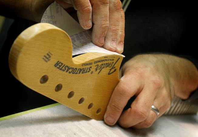 A Fender Stratocaster head stock is sanded in the Fender Custom Shop at the factory in Corona, Calif. on Tuesday, Oct. 15, 2013. Leo Fender developed the instrument in a small workshop in Fullerton, Calif. six decades ago.