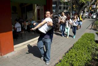 A woman is carried at the Juarez neighborhood after a strong earthquake jolted Mexico City, Friday, April 18, 2014. The powerful magnitude-7.2 earthquake shook central and southern Mexico but there were no early reports of major damage or casualties.