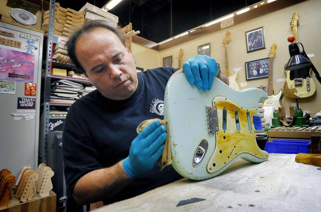 Fender Custom Shop Master Builder John Cruz works on a heavily-used Fender Stratocaster body at the Fender factory in Corona, Calif. on Tuesday, Oct. 15, 2013. Leo Fender developed the instrument in a small workshop in Fullerton, Calif. six decades ago.