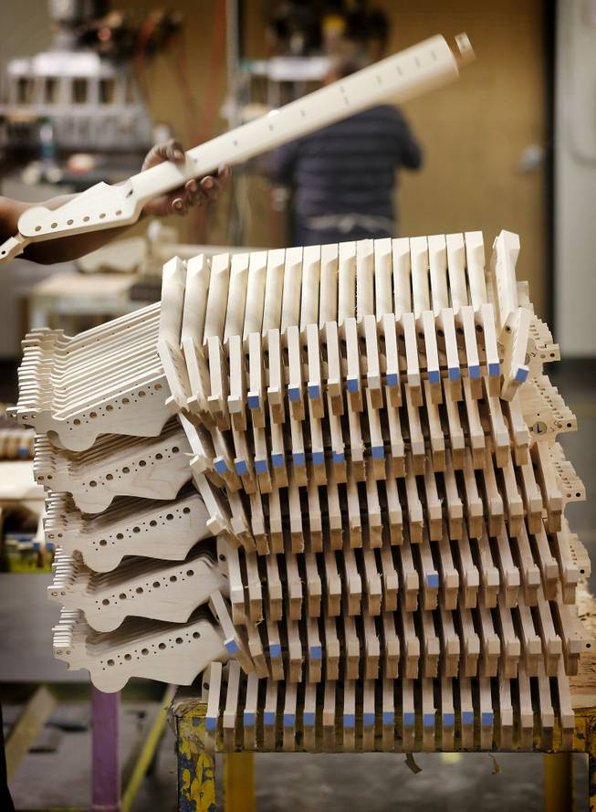 Fender Stratocaster electric guitar necks are prepared for assembly at the Fender factory in Corona, Calif. Leo Fender developed the instrument in a small workshop in Fullerton, Calif. six decades ago.
