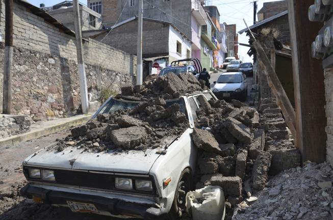 A parked car suffered damage when a adobe wall collapsed on it after a strong earthquake shook Chilpancingo, Mexico, Friday morning, April 18, 2014. A powerful magnitude-7.2 earthquake shook central and southern Mexico but there were no early reports of major damage or casualties.