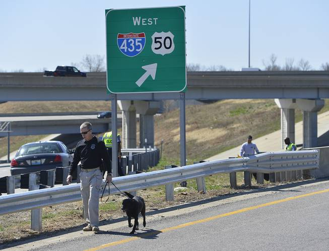 In this photo taken on Wednesday, April 9, 2014, Kansas City police and agents from the Alcohol, Tobacco and Firearms with canines investigate a shooting along southbound Interstate 435 in Kansas City, Mo.