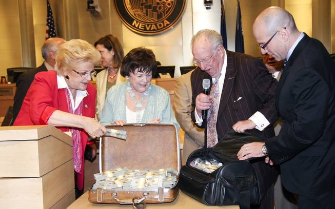 This image provided by the city of Las Vegas shows, from left, Mayor Carolyn G. Goodman, Councilwoman Lois Tarkanian, Oscar B. Goodman and The Mob Museum Executive Director Jonathan Ullman, displaying the $1.5 million in cash paid to the city at a council meeting on April 16, 2014.