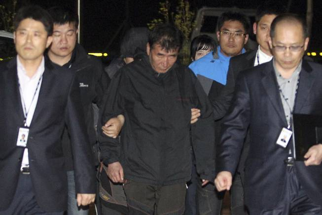 Lee Joon-seok, center, the captain of the sunken ferry Sewol in the water off the southern coast, arrives at a court which issues his arrest warrant in Mokpo, south of Seoul, South Korea, Friday, April 18, 2014.