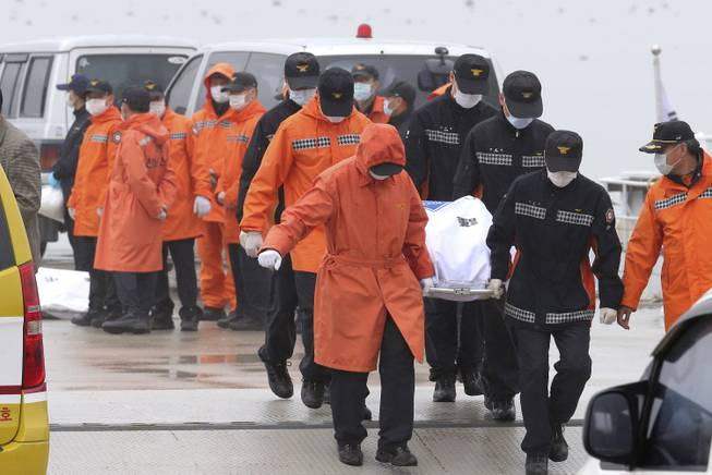 Rescue workers carry the body of a passenger aboard The Sewol ferry which sank in the water off the southern coast, at a port in Jindo, South Korea, Friday, April 18, 2014.