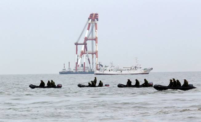 South Korean navy personnel on boats search passengers of the sunken ferry Sewol in the water off the southern coast near Jindo, south of Seoul, South Korea, Saturday, April 19, 2014.
