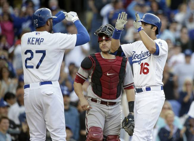 Los Angeles Dodgers outfielders Andre Ethier, right, and Matt Kemp, left, celebrate a three-run home run hit by Ethier in front of Arizona Diamondbacks catcher Miguel Montero during the fourth inning of a baseball game Saturday, April 19, 2014, in Los Angeles.