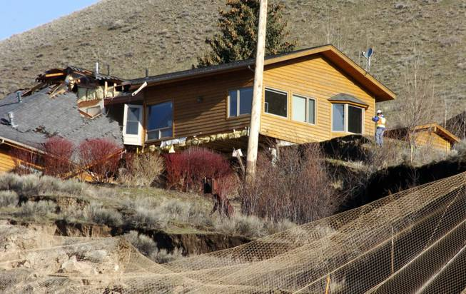 A worker inspects damage to a house at the top of a slow-motion landslide in Jackson, Wyo., on Saturday, April 19, 2014.