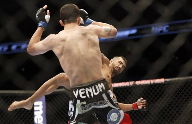 Estevan Payan, right, and Alex White fight in a mixed martial arts event on Saturday, April 19, 2014, at UFC Fight Night in Orlando, Fla. White won.