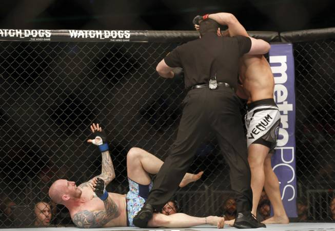 The referee stops the fight in the first round between Luke Zachrich, bottom, and Caio Magalhaes of Brazil in a mixed martial arts event on Saturday, April 19, 2014, at UFC Fight Night in Orlando, Fla. Magalhaes won.