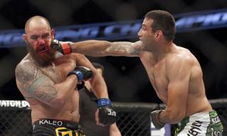 Fabricio Werdum, right, hits Travis Browne during a UFC mixed martial arts bout on Saturday, April 19, 2014, in Orlando, Fla. Werdum won.