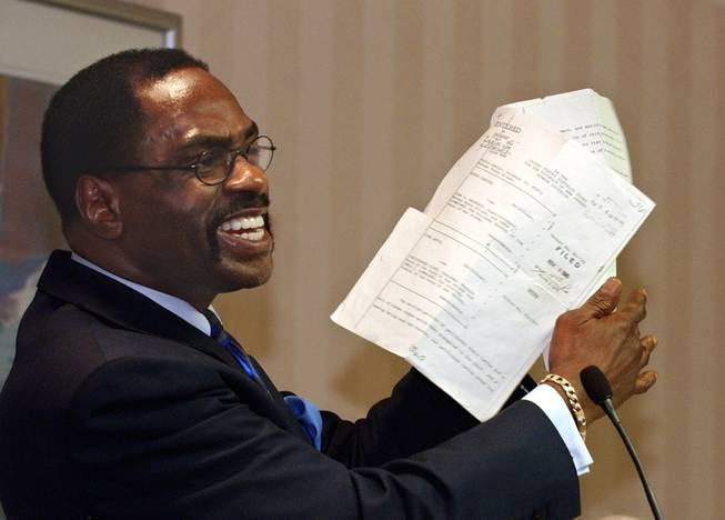 "In this Jan. 29, 2004, file photo, former boxer Rubin ""Hurricane"" Carter holds up the writ of habeas corpus that freed him from prison during a news conference held in Sacramento, Calif. Carter, who spent almost 20 years in jail after twice being convicted of a triple murder he denied committing, died at his home in Toronto, Sunday, April 20, 2014, according to long-time friend and co-accused John Artis. He was 76."
