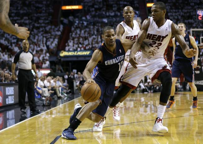 Charlotte Bobcats' Gary Neal (12) drives to the basket as Miami Heat's James Jones (22) defends during the second half in Game 1 of an opening-round NBA basketball playoff series on Sunday, April 20, 2014, in Miami. The Heat defeated the Bobcats 99-88.