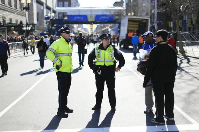 Police stand by near the finish line ahead of Monday's 118th Boston Marathon on April 20 in Boston. Massachusetts Gov. Deval Patrick says officials are striking a balance between more security and maintaining the city's festive spirit.