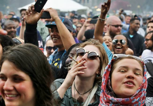 With the Colorado state capitol building visible in the background, partygoers dance to live music and smoke pot on the first of two days at the annual 4/20 marijuana festival in Denver on April 19, 2014. The annual event is the first 420 marijuana celebration since retail marijuana stores began selling in January 2014.