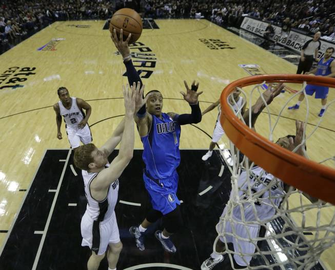 Dallas Mavericks' Monta Ellis (11) drives to the basket between San Antonio Spurs' Matt Bonner, left, and Tim Duncan, right, during the first quarter of Game 1 of the opening-round NBA basketball playoff series, Sunday, April 20, 2014, in San Antonio.