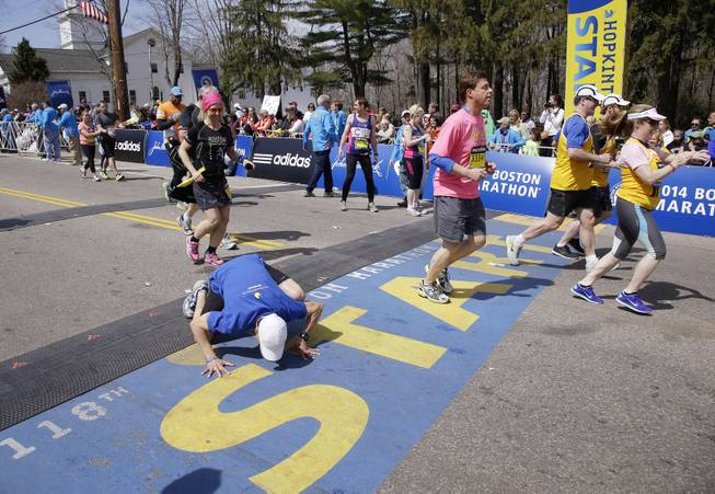 A runner toward the back of the fourth and last wave of competitors kneels to kiss the start line as he begins his running of the 118th Boston Marathon, Monday, April 21, 2014, in Hopkinton, Mass.