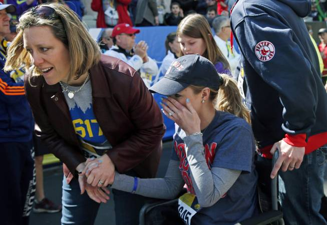 Survivor Rebekah Gregory DiMartino, center, wipes tears as she is led in her wheelchair after crossing the finish line of the Boston Marathon Tribute Run in Boston, Saturday, April 19, 2014.