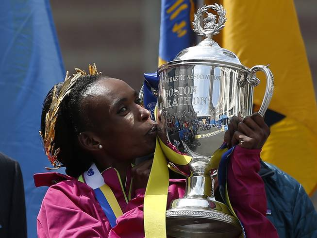 Rita Jeptoo, of Kenya, kisses the trophy after winning the women's division of the 118th Boston Marathon Monday, April 21, 2014 in Boston.