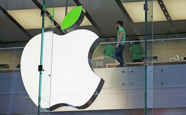 Employees wear green shirts near Apple's familiar logo displayed with a green leaf at the Apple Store timed to coincide with an annual celebration of Earth Day in Sydney, Tuesday, April 22, 2014.