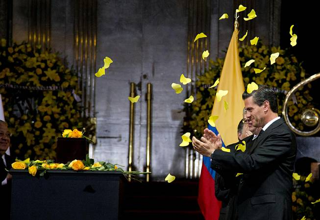 Yellow paper butterflies fall as Mexico's President Enrique Pena Nieto stands next to the urn containing the ashes of Colombian Nobel Literature laureate Gabriel Garcia Marquez during the authors homage at the Palace of Fine Arts in Mexico City, Monday, April 21, 2014.