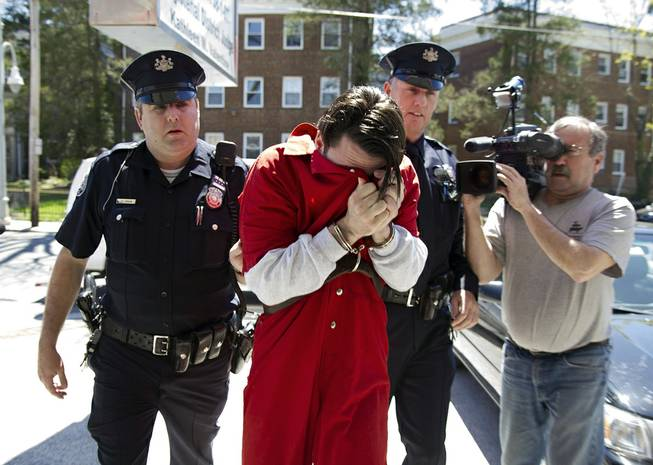 Neil K. Scott covers his face as he is led into Montgomery County Magisterial District Court, Monday, April 21, 2014, in Montgomery County, Pa.
