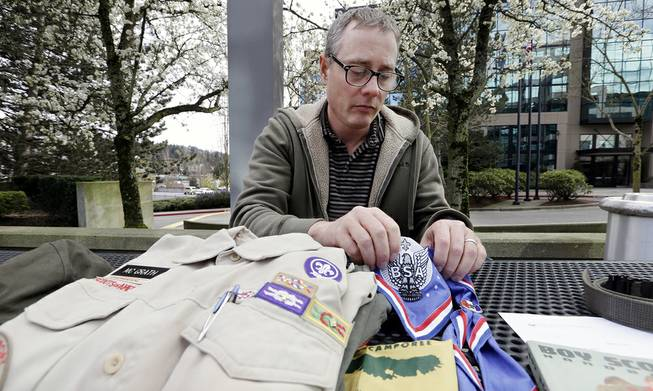 Geoff McGrath displays a vintage Boy Scout Handbook given him as a gift by one of the boys in the Seattle troop he led in Bellevue, Wash., April 1, 2014.