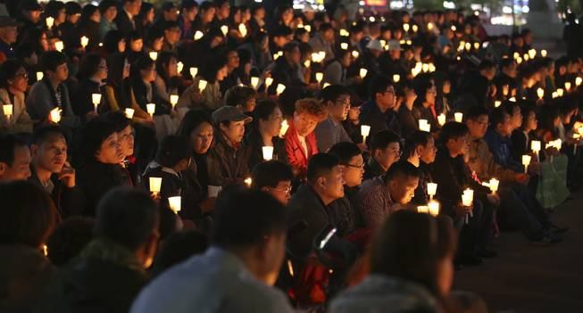 South Koreans hold candles during a prayer for people believed to have been trapped in the sunken ferry Sewol, in Ansan, South Korea, Monday, April 21, 2014.