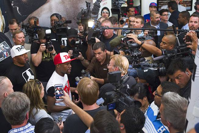 WBC welterweight champion Floyd Mayweather Jr. is surrounded by reporters before a media workout at the Mayweather Boxing Club Tuesday, April 22, 2014. Mayweather is preparing for his fight against WBA champion Marcos Maidana of Argentina at the MGM Grand Garden Arena on May 3.
