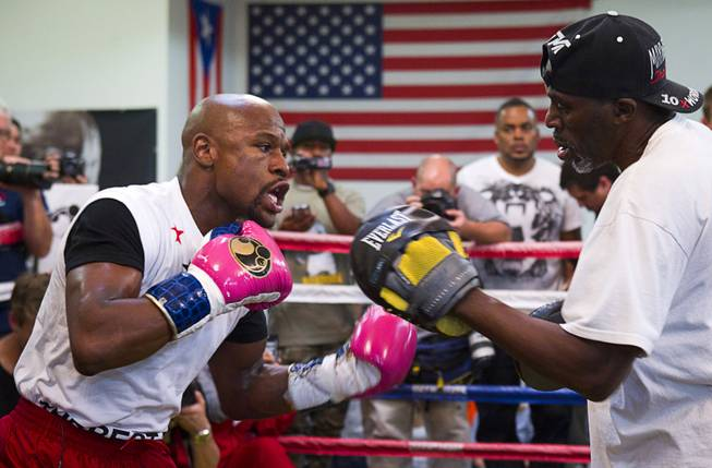 WBC welterweight champion Floyd Mayweather Jr., left, works on his timing with his uncle and trainer Roger Mayweather at the Mayweather Boxing Club Tuesday, April 22, 2014. Mayweather is preparing for his fight against WBA champion Marcos Maidana of Argentina at the MGM Grand Garden Arena on May 3.