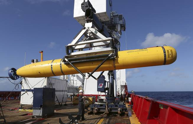 In this Thursday, April 17, 2014, photo provided by the Australian Defense Force, the Phoenix International Autonomous Underwater Vehicle (AUV) Artemis is craned over the side of Australian Defense Vessel Ocean Shield before launching the vehicle into the southern Indian Ocean in the search of the missing Malaysia Airlines Flight 370.