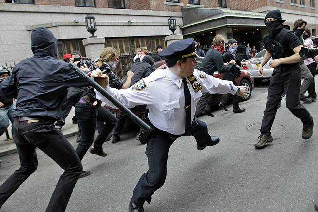 A police lieutenant swings his baton at Occupy Wall Street activists in New York, May 1, 2012. This photo is among the many put on Twitter in response to a New York Police Department request for Twitter users to share pictures of themselves posing with police officers.
