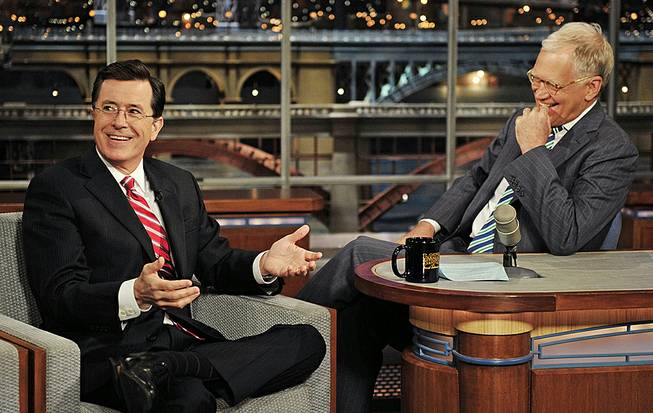 "In this May 3, 2012, photo, Stephen Colbert, host of the ""Colbert Report"" on Comedy Central, has a laugh onstage with host David Letterman on the set of ""The Late Show With David Letterman."""