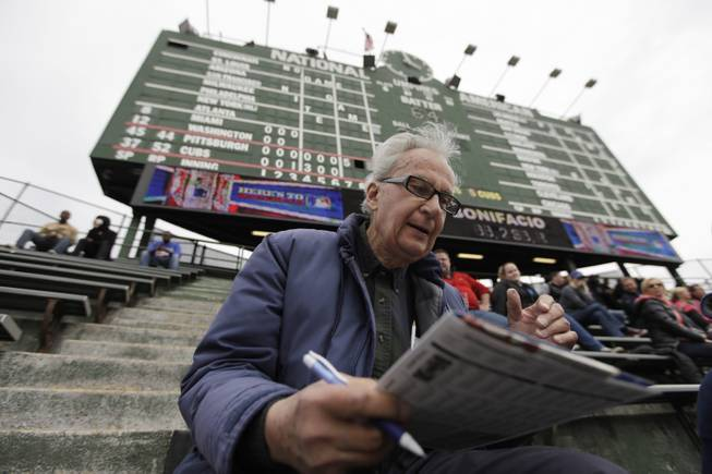 In this April 10, 2014 photo, John Weber keeps score with a pencil and scorecard as he watches a baseball game between Pittsburgh Pirates and Chicago Cubs at Wrgley Field Thursday, in Chicago. The 86-year-old retired transit worker figures he is an increasingly rare kind of baseball fan. Between batters and between pitches, most fans in the stands at Wrigley _ and everywhere else in the majors _ take their eyes off the game to peck away at smartphones, not bothering to try to figure out the baseball hieroglyphics that Weber and other purists scrawl on their cards.