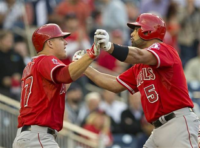 Los Angeles Angels Albert Pujols, right, is congratulated by teammate Mike Trout, left, after hitting a three-run homer off Washington Nationals starting pitcher Taylor Jordan during the first inning of a baseball game in Washington, Tuesday, April 22, 2014. It was Pujols 499th home run of his career. Later in the game, Pujols added his 500th-career home run.