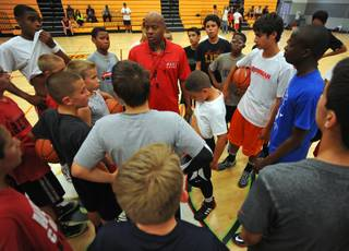 Former UNLV Runnin' Rebels point guard Dedan Thomas, center, instructs members of his youth team during a practice session held at Western Tech High School on Tuesday, April 22, 2014.