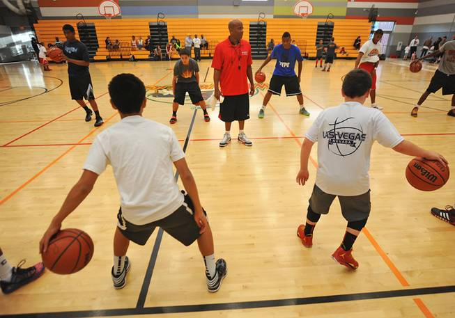 UNLV alumni Dedan Thomas supervises a youth basketball team as they conduct dribbling drills during a practice session in the Western Tech High School gymnasium on Tuesday, April 22, 2014.